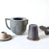 Théière individuelle grise en céramique, accompagnée de son filtre et couvercle
